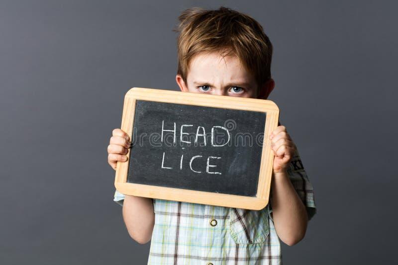 Criança desagradada que esconde atrás de uma ardósia da escola que scaring os piolhos principais foto de stock