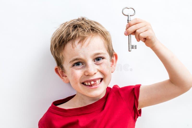 Criança desdentado Giggling que guarda chave para o conceito da ideia do divertimento foto de stock royalty free