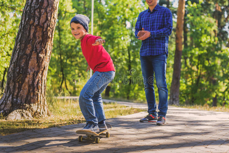 Criança despreocupada que está no skate perto do pai foto de stock royalty free