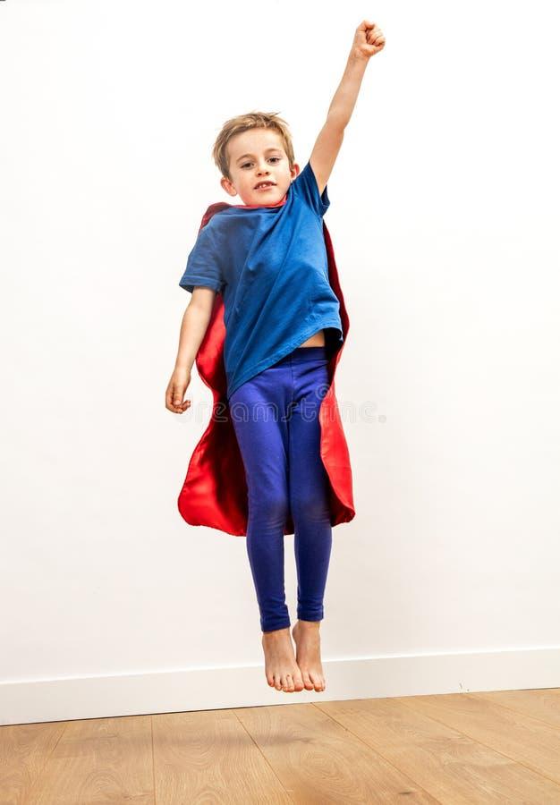 Criança dinâmica que alcança altamente como um super-herói poderoso, voando imagem de stock