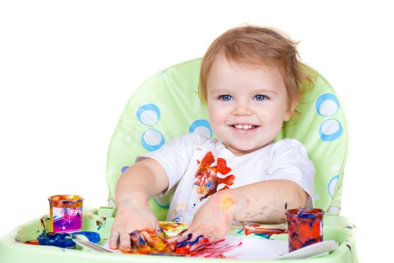 A criança do bebê cria a arte com as pinturas foto de stock