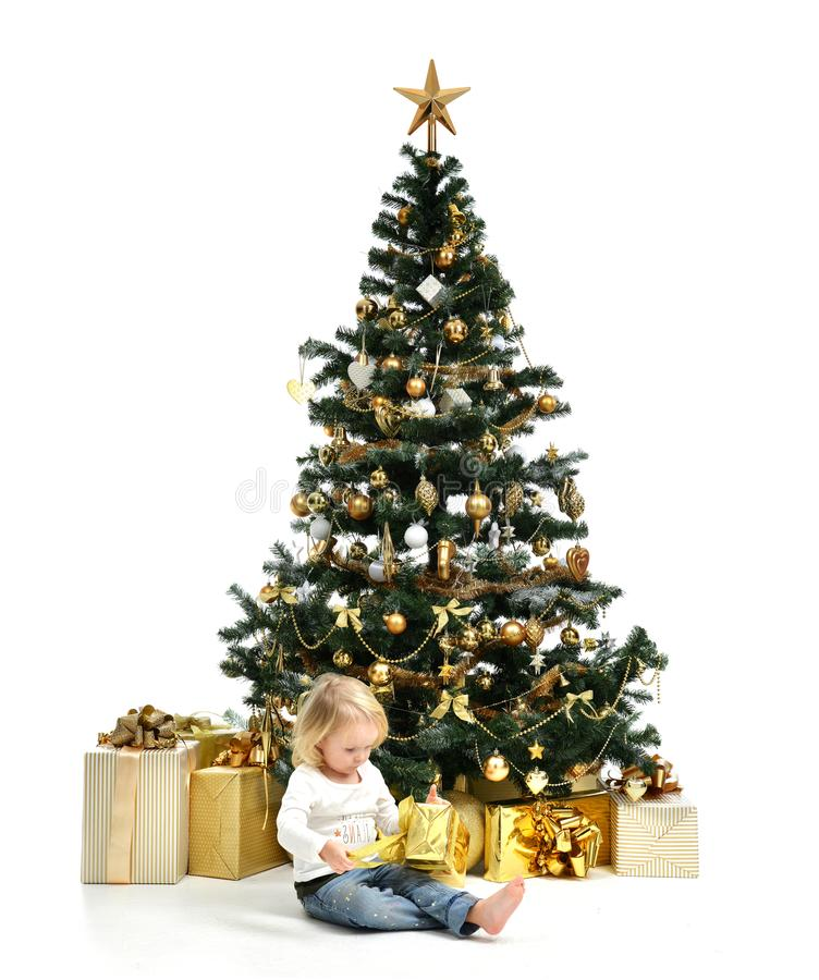 Criança do bebê da criança que senta-se sob a árvore de Natal decorada do ouro com o presente dos retalhos do ouro fotos de stock