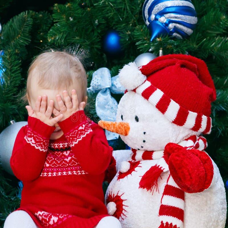 Criança do bebê no vestido vermelho que senta-se pela árvore do ano novo com o brinquedo do boneco de neve que fecha-se cobrindo  fotos de stock