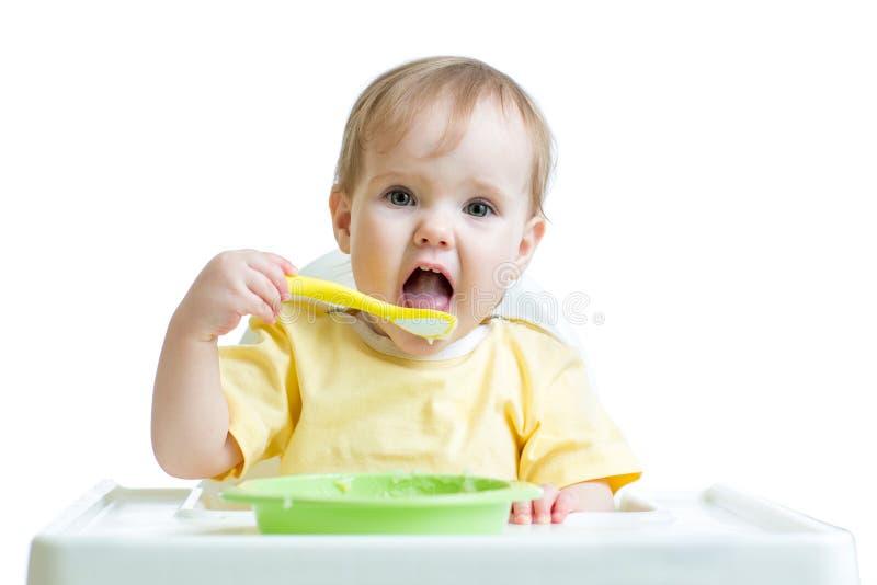 Criança do bebê que come o alimento saudável com uma colher foto de stock
