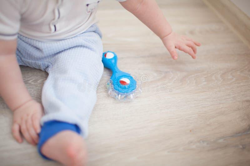 Criança do bebê que senta-se e que joga com brinquedo imagens de stock
