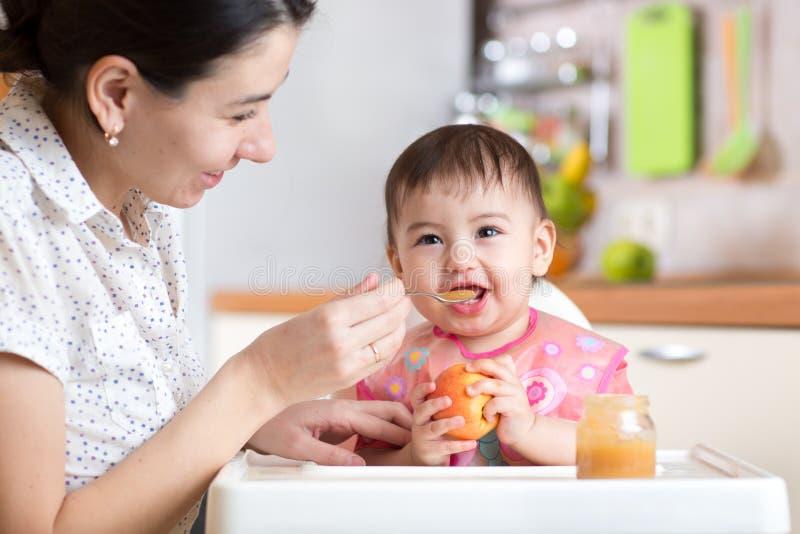Criança do bebê que senta-se na cadeira com uma colher e que come o alimento saudável imagens de stock