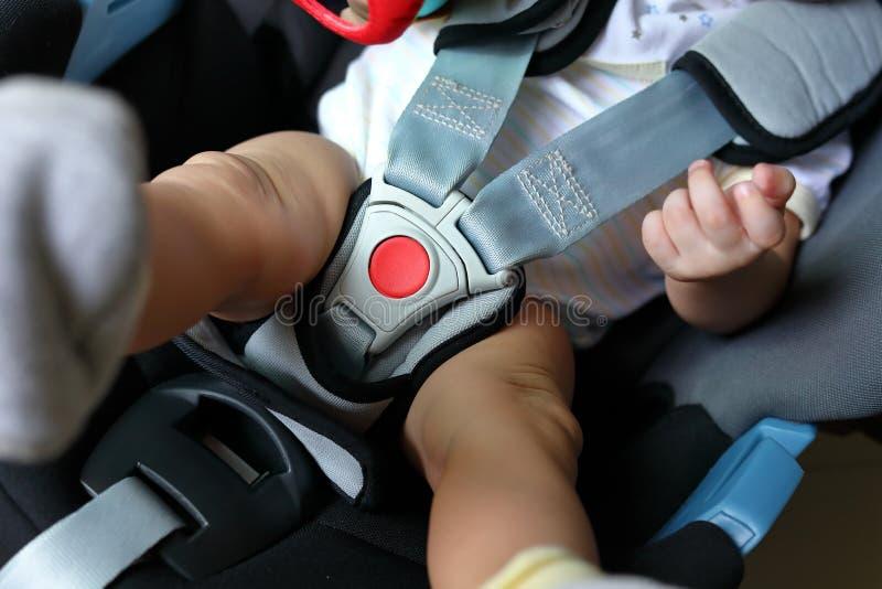 Criança do bebê que senta-se no banco de carro com a correia de segurança fechado fotos de stock royalty free