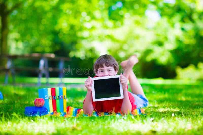 Criança do estudante com o tablet pc na jarda de escola imagem de stock royalty free