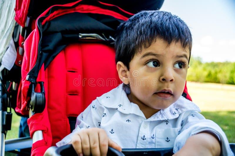 Criança do Latino em um carrinho de criança foto de stock