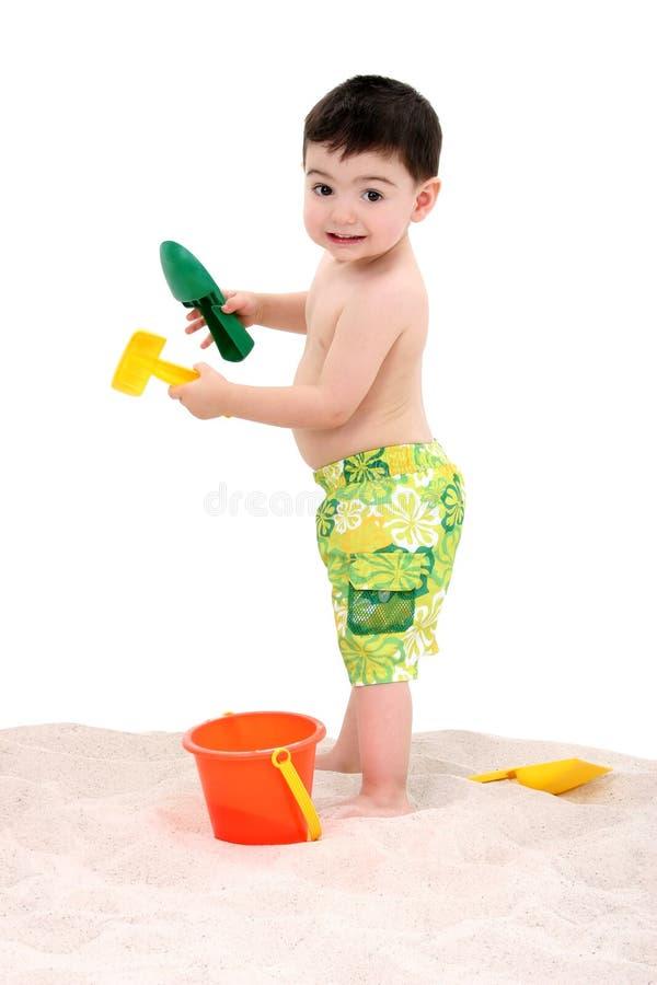 Criança do menino da praia com os brinquedos na areia foto de stock