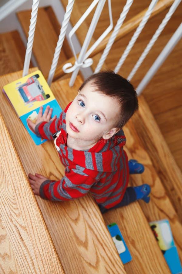 criança do menino dois anos velha com os livros de crianças que escalam na escada dentro fotografia de stock