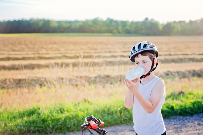 Criança do menino na água potável branca do capacete da bicicleta fotos de stock royalty free