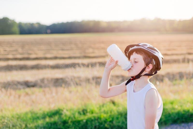 Criança do menino na água potável branca do capacete da bicicleta foto de stock royalty free