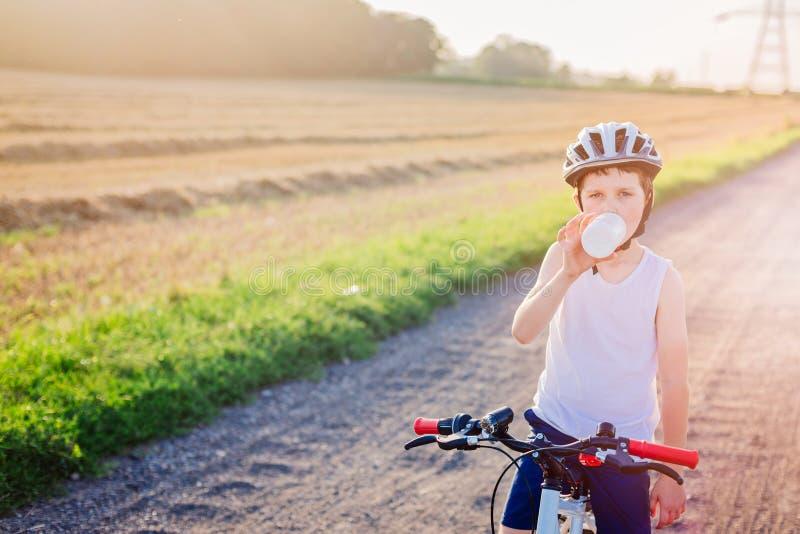 Criança do menino na água potável branca do capacete da bicicleta imagens de stock royalty free