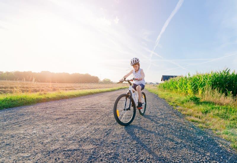 Criança do menino na equitação branca do capacete da bicicleta na bicicleta fotografia de stock