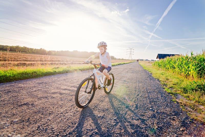 Criança do menino na equitação branca do capacete da bicicleta na bicicleta imagens de stock