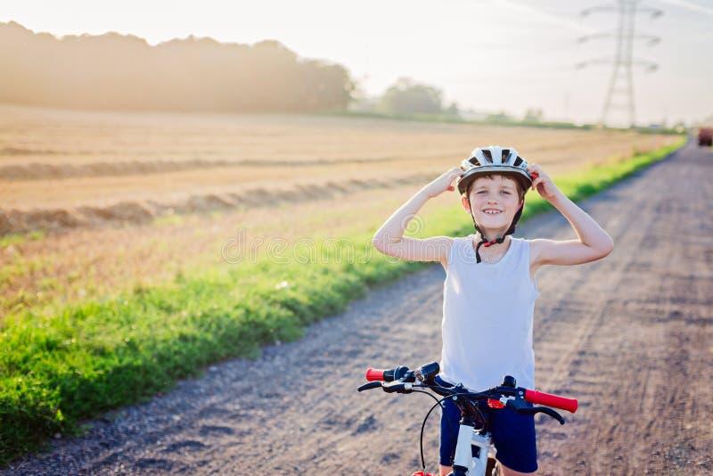 Criança do menino na equitação branca do capacete da bicicleta na bicicleta fotografia de stock royalty free