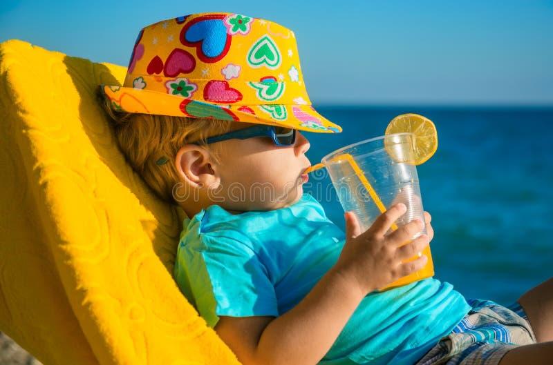 Criança do menino na poltrona com vidro do suco na praia fotos de stock