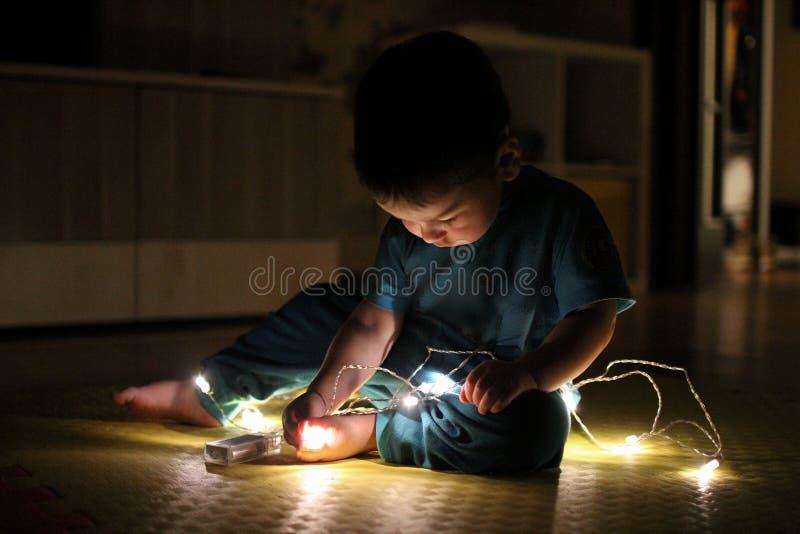 A criança do menino na roupa azul que senta-se no tapete amarelo com Chr imagens de stock royalty free