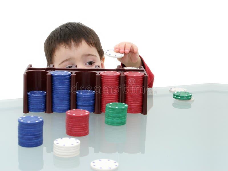 Criança do menino que joga com microplaquetas do póquer foto de stock royalty free