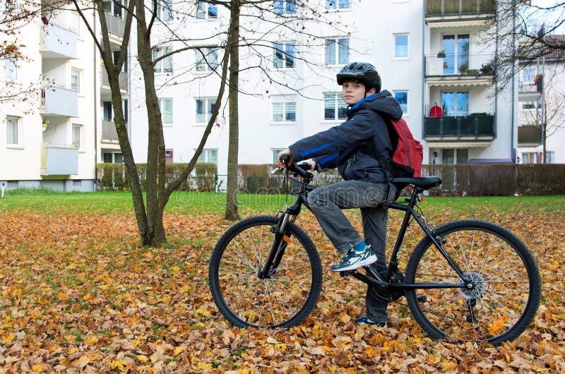 Criança do menino que monta uma bicicleta imagens de stock