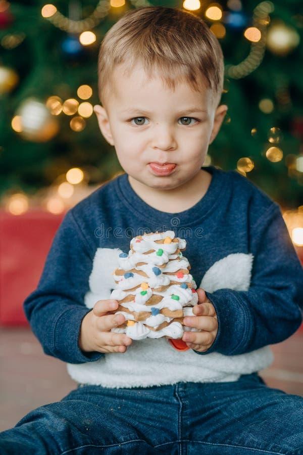 A criança do Natal do ano novo do feriado come o bolo delicioso foto de stock
