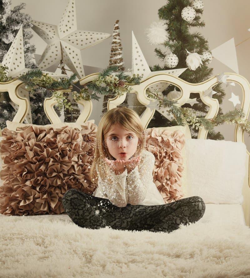 Criança do Natal no desejo de sopro da neve da cama branca foto de stock