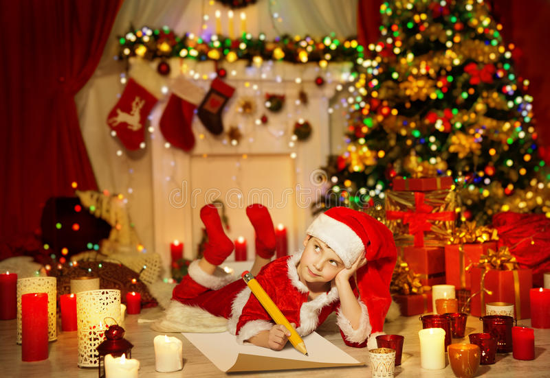 A criança do Natal redige a lista de objetivos pretendidos, criança Santa Hat Writing Letter fotos de stock