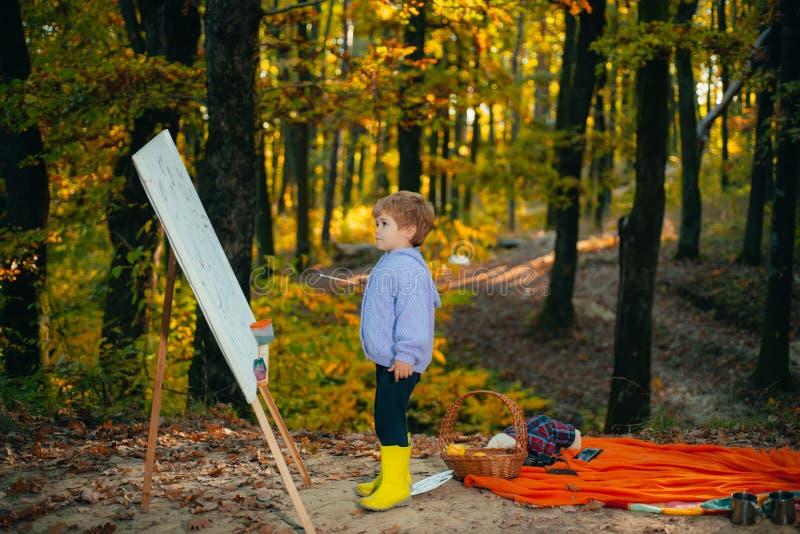 Criança do outono Imagem nova do come?o Pintor com arma??o e lona Rapaz pequeno bonito na pintura da floresta suas primeiras pint foto de stock