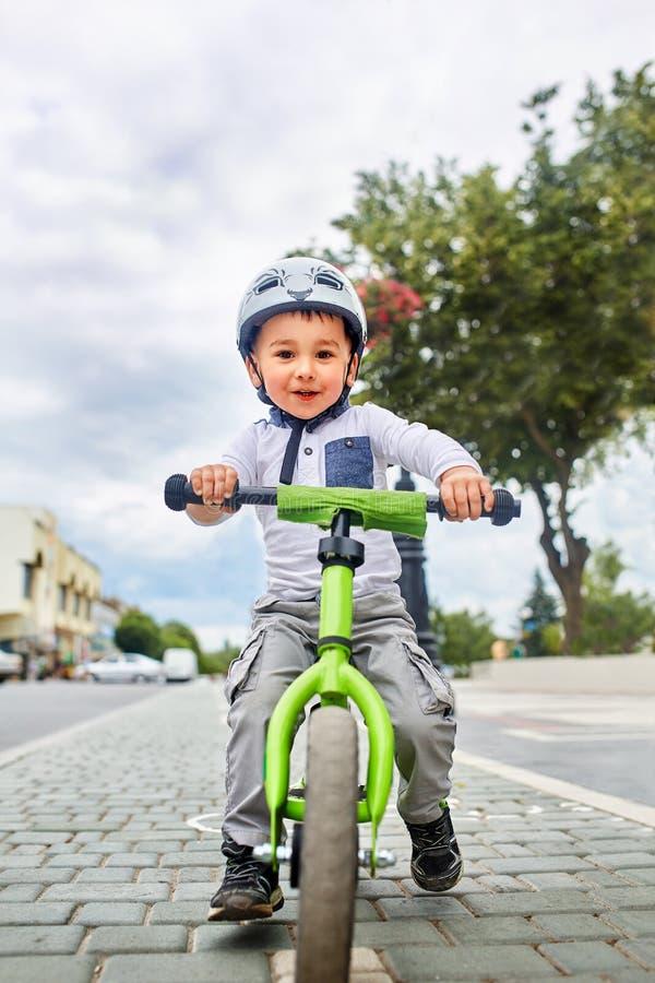 Criança do rapaz pequeno no passeio do capacete uma bicicleta no parque da cidade Criança alegre exterior fotos de stock
