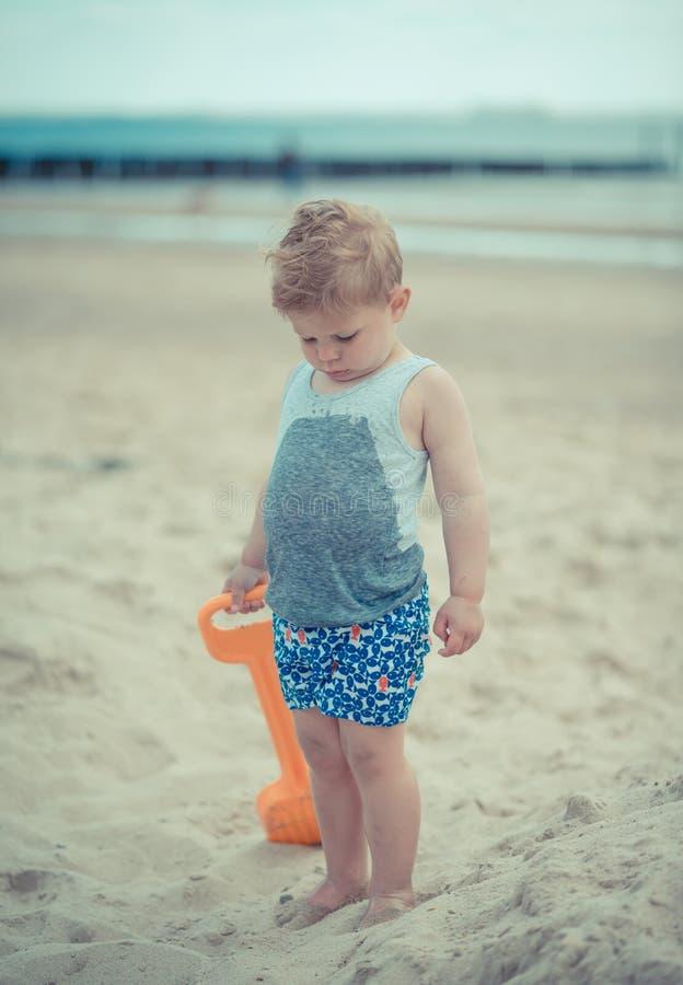 Criança do rapaz pequeno que está com uma camisa molhada na praia foto de stock