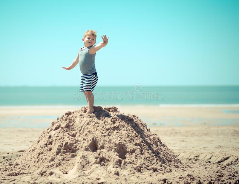 Criança do rapaz pequeno que está em um monte na praia com seus braços fotos de stock