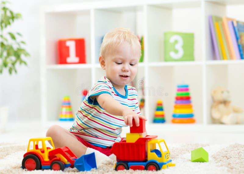 Criança do rapaz pequeno que joga com carro do brinquedo imagens de stock