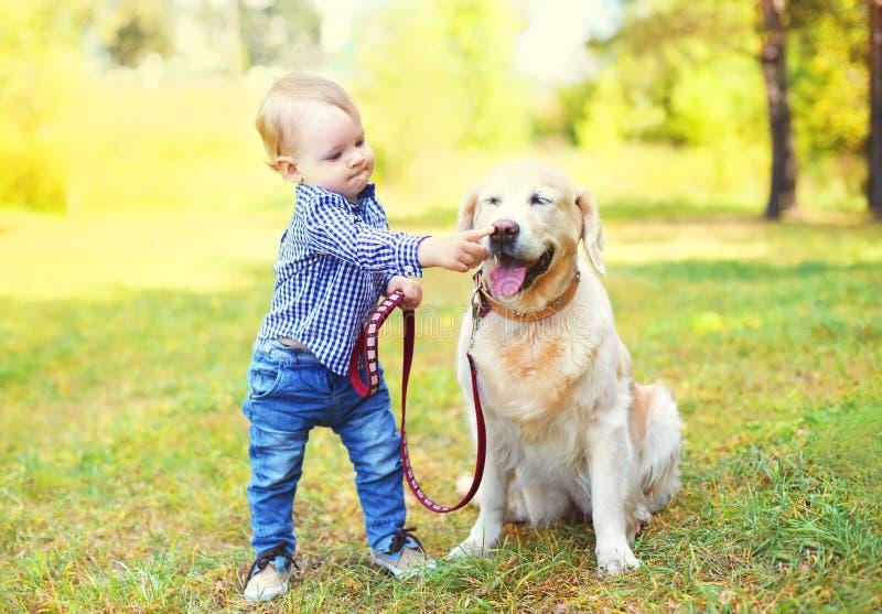 Criança do rapaz pequeno que joga com o cão do golden retriever na grama fotografia de stock