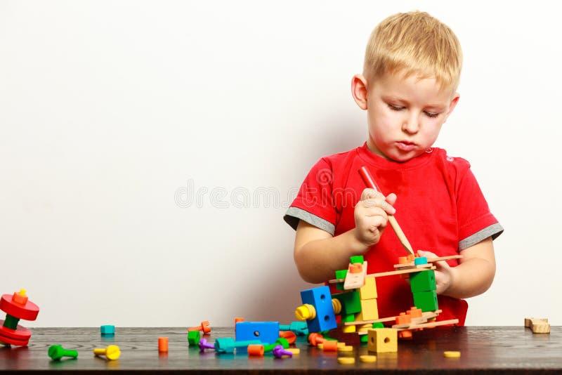 Criança do rapaz pequeno que joga com os brinquedos dos blocos de apartamentos interiores imagens de stock royalty free