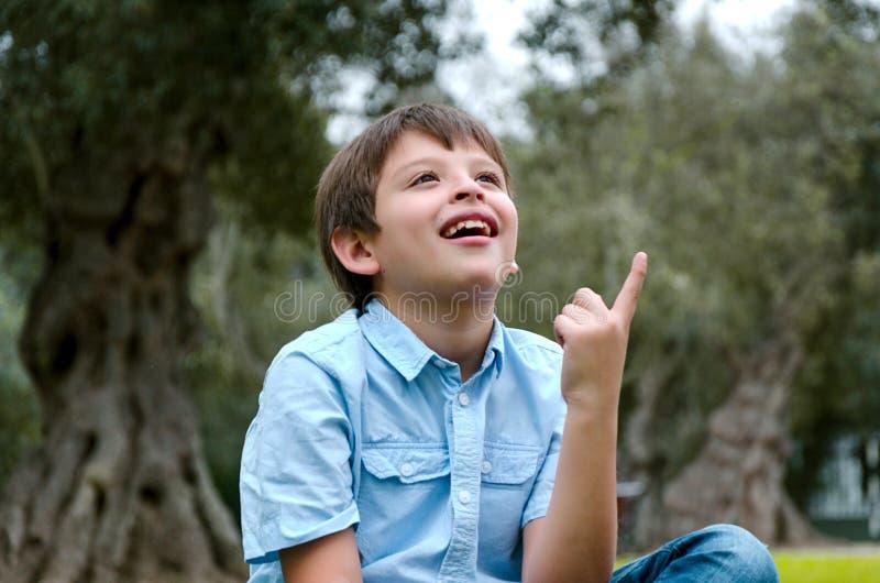 A criança do retrato com cabelo louro tem uma ideia, apontando com dedo acima imagens de stock