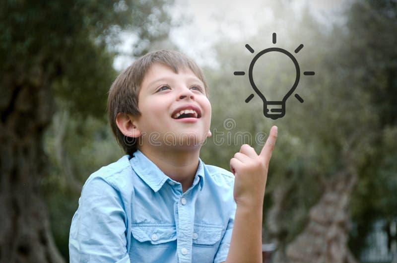 A criança do retrato com cabelo louro tem uma ideia, apontando com dedo acima fotos de stock royalty free