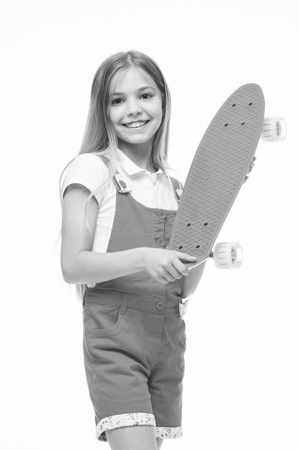 Criança do skate no fato-macaco cor-de-rosa Sorriso pequeno da menina com a placa do patim isolada no branco Skater da criança qu imagem de stock