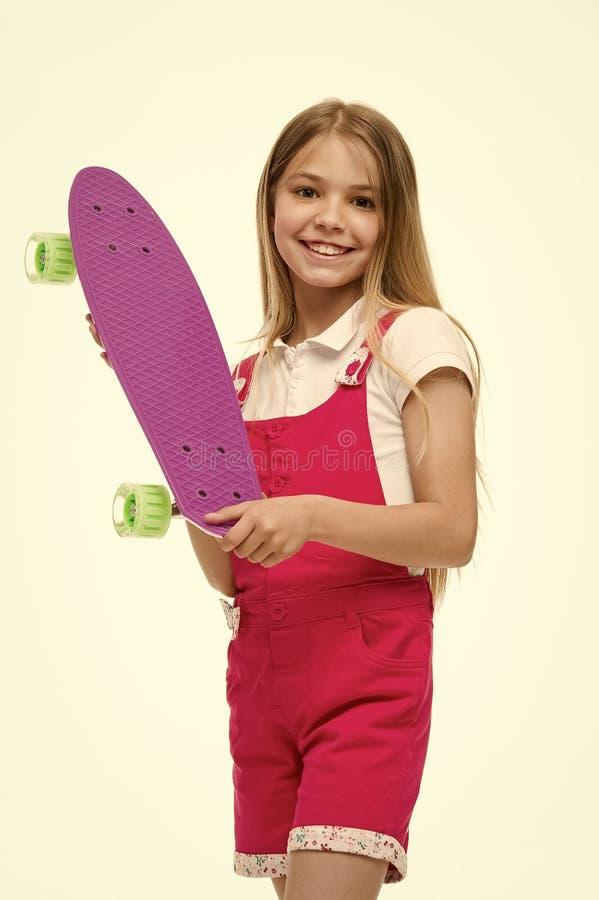 Criança do skate no fato-macaco cor-de-rosa Sorriso pequeno da menina com a placa do patim isolada no branco Skater da criança qu fotos de stock