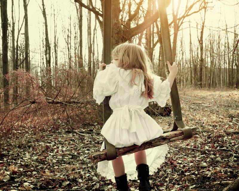 Criança do vintage que senta-se no balanço velho nas madeiras apenas foto de stock royalty free