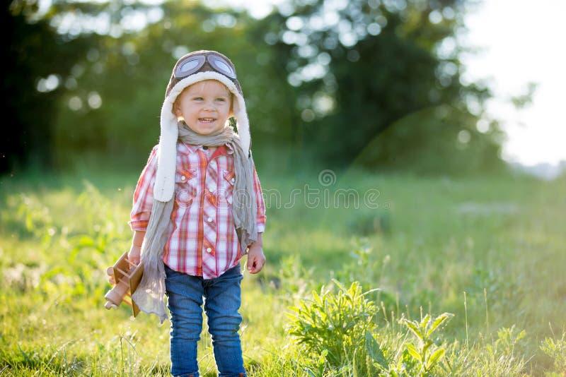 Criança doce, criança brincando com avião em campo de papoila, lindo pôr do sol fotografia de stock