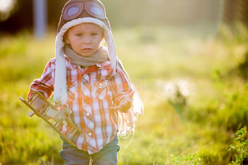 Criança doce, criança brincando com avião em campo de papoila, lindo pôr do sol foto de stock