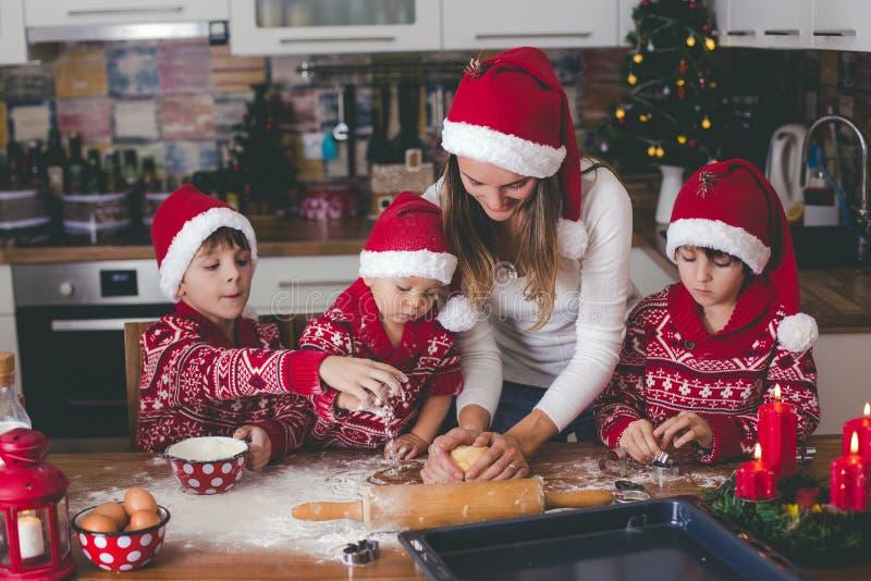 Criança doce da criança e seu irmão mais idoso, meninos, mamã de ajuda que prepara cookies do Natal em casa imagem de stock royalty free