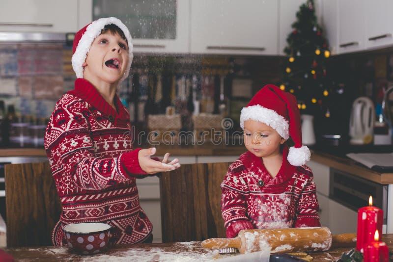 Criança doce da criança e seu irmão mais idoso, meninos, mamã de ajuda que prepara cookies do Natal em casa imagens de stock royalty free