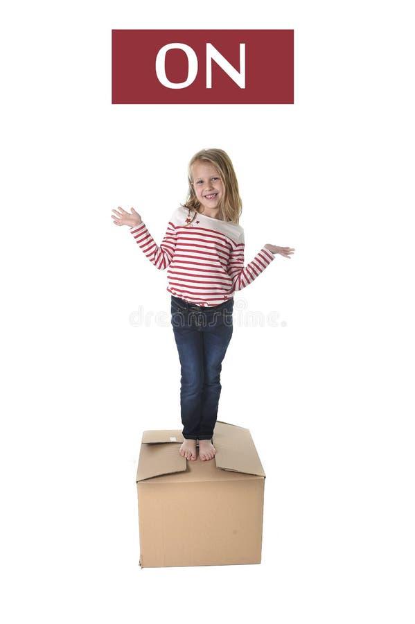 Criança doce do cabelo louro que stading sobre a caixa de cartão isolada no fundo branco em aprender o inglês fotos de stock