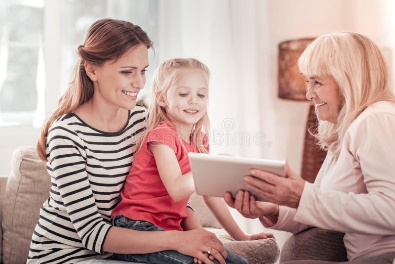 Criança doce em um t-shirt vermelho que mostra imagens em uma tabuleta fotografia de stock royalty free