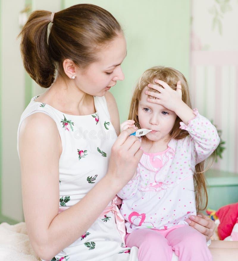 Criança doente com febre alta e mãe que tomam a temperatura imagens de stock