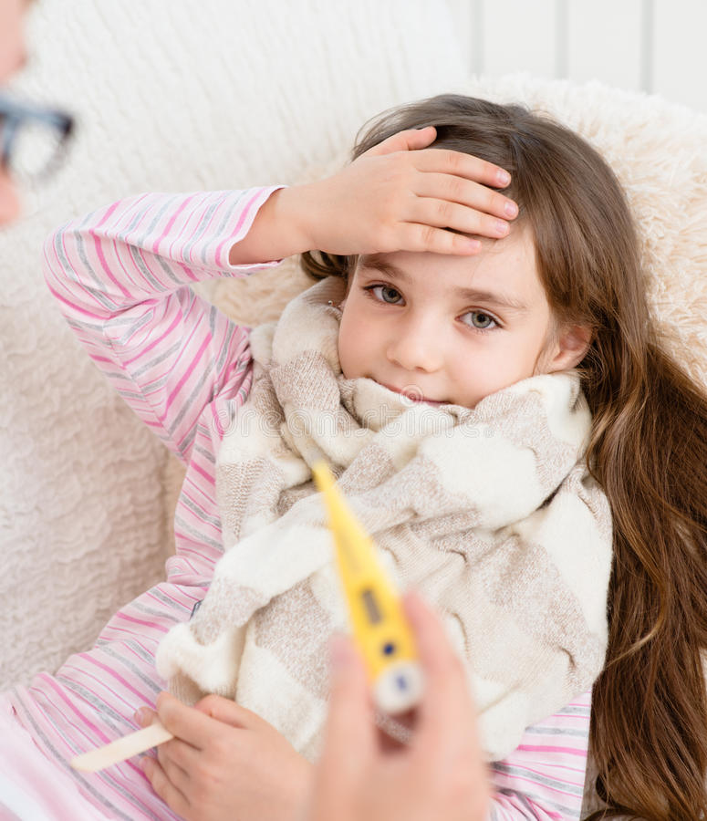 Criança doente com a febre alta que coloca na cama e na mãe que tomam a temperatura fotos de stock royalty free