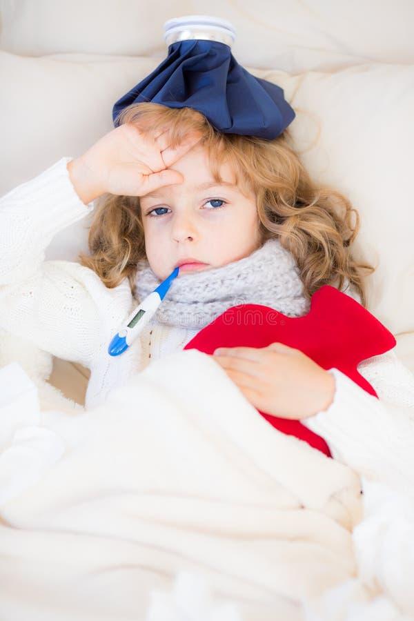 Criança doente com febre e a garrafa de água quente fotografia de stock royalty free