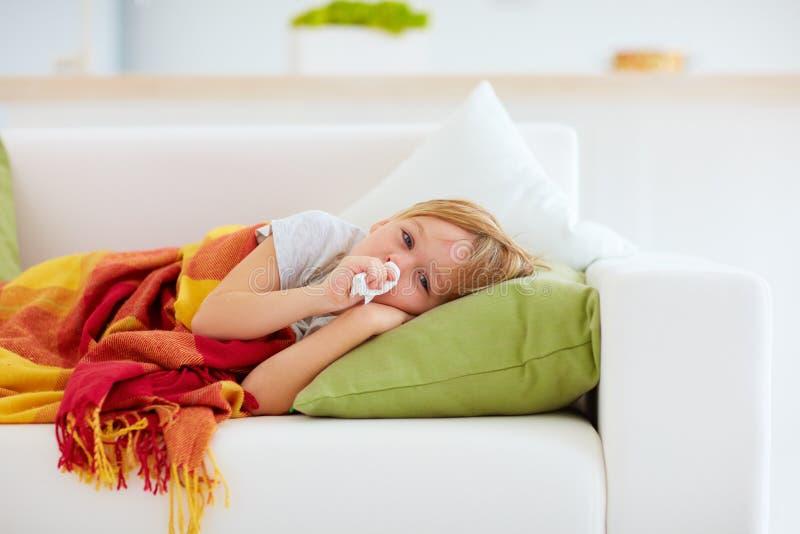 Criança doente com nariz ralo e calor de febre que encontra-se no sofá em casa fotografia de stock royalty free
